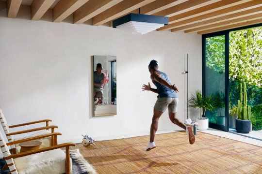 Smart mirror with black man energetically exercising in living room