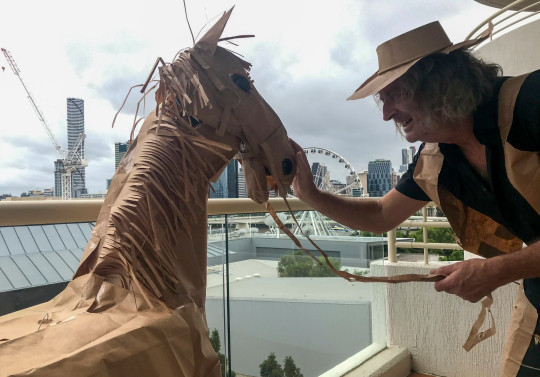David Marriott on a balcony with his paper horse.  David Marriott has kept himself entertained  during his hotel quarantine at Rydges South Bank hotel in Brisbane, Australia.