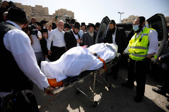 Mourners gather around the body of Rabbi Eliezer Goldberg, who died during Lag BaOmer celebrations at Mt. Meron in northern Israel, just before his funeral in Jerusalem on Friday, April 30, 2021. A stampede at a religious festival attended by tens of thousands of ultra-Orthodox Jews in northern Israel killed dozens of people and injured about 150 early Friday, medical officials said. It was one of the country's deadliest civilian disasters. (AP Photo/Ariel Schalit)