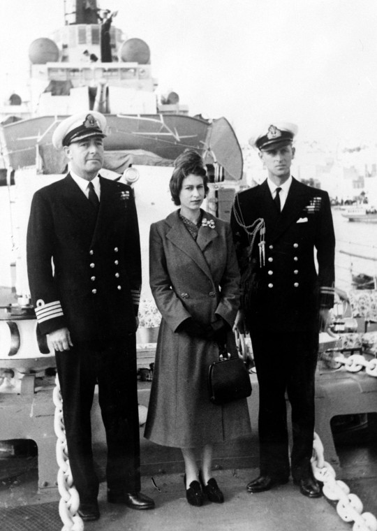 File photo dated 26/12/49 of The Duke of Edinburgh and Captain John Edwin Home McBeath DSO, DSC, RN (left), pose with Queen Elizabeth II for a photograph on HMS Chequers, during the Boxing Day visit to the destroyer that the Duke is currently serving on. Philip joined the Navy after leaving school and in May 1939 enrolled at the Royal Naval College in Dartmouth, where he was singled out as best cadet. He rose rapidly through the ranks, earning promotion after promotion, but his life was to take a very different course. The duke?s flourishing naval career came to a premature end in 1951. Philip stepped down from his active role in the forces to fulfil his duty as consort. Issue date: Friday April 4, 2021. PA Photo. Had the Duke of Edinburgh not become the Queen?s husband, some believe he would have been First Sea Lord ? the professional head of the Royal Navy. See PA story ROYAL Philip Navy. Photo credit should read: PA/PA Wire