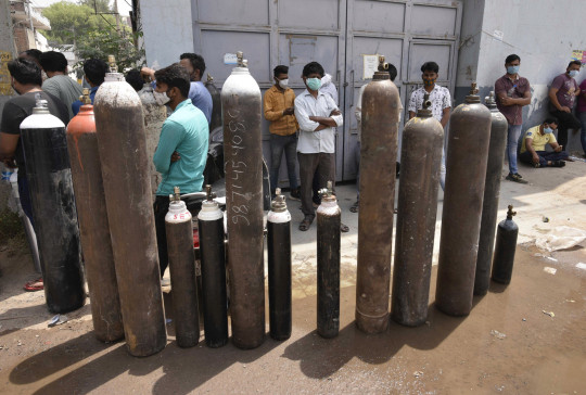 SIPA USA via PA Images MANESAR, INDIA - APRIL 28: Family members of Covid-19 patients waiting to refill empty oxygen cylinders outside a filling center on April 28, 2021 in Manesar, India. India, in the last 24 hours, recorded 3,60,960 fresh Covid-19 cases and 3,293 deaths, which is the highest in the country so far. With today?s numbers, the total number of coronavirus cases rose to 1,79,97,267 and the number of fatalities reached 2,01,187. At present, there are 29,78,709 active cases in India and as many as 1,48,17,371 people have recovered. As Covid-19 cases continued to surge in India people are struggling to get hospital beds, ventilators, oxygen cylinders, injections and medicines with the health infrastructure in the state almost stretched to its limit. (Photo by Vipin Kumar/Hindustan Times/Sipa USA)