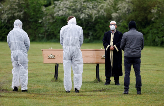 An Imam wearing a mask stands near the coffin of Munuse Nabi, who died from the coronavirus disease (COVID-19), during her funeral at a cemetery in London, Britain, April 28, 2020. Picture taken April 28, 2020. To match Special Report HEALTH-CORONAVIRUS/BRITAIN-ELDERLY REUTERS/Peter Nicholls
