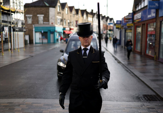 W. Uden & Sons Funeral Conductor Spencer Baxter leads the procession of a funeral service in Sidcup, amid the coronavirus disease (COVID-19) pandemic, in south east London, Britain, January 28, 2021. Picture taken January 28, 2021. REUTERS/Hannah McKay