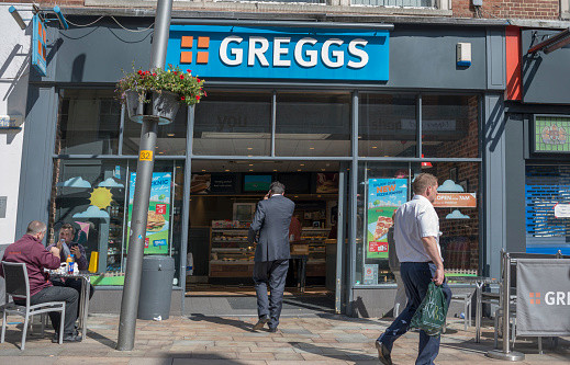 The outside of a Greggs bakery on a high street, as a man in a suit enters the store.