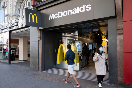 A McDonalds store front on a London high street, with two people in facemasks walking past.