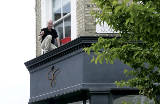 Actor Ade Edmondson has been pictured hitting rock bottom after being rescued by fire crews - for getting stuck while cleaning his windows. See SWNS story SWBRbottom. The hapless celebrity was photographed stuck on a ledge pleading for help from passer-bys. His calls were heard by Duncan Cumming, 46, who phoned the fire brigade who sent a crew to to Ade's rescue. The 64-year-old TV star later shared his ordeal on social media and said a small crowd had gathered to watch the drama unfold.