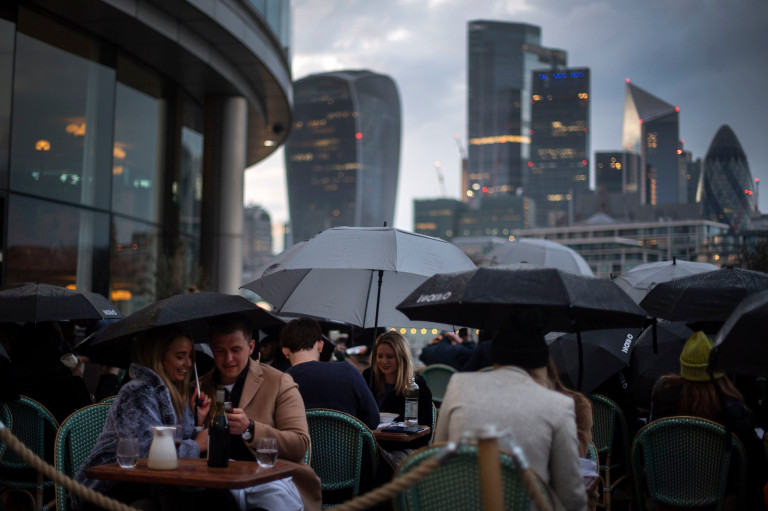 People endure the wet and windy Bank Holiday weekend weather to sit outside a restaurant near Tower Bridge in central London. Picture date: Monday May 3, 2021. PA Photo. See PA story HEALTH Coronavirus. Photo credit should read: Victoria Jones/PA Wire