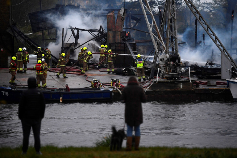Bystanders look on as firefighters tackle a blaze at a boatyard next to the River Thames, Hampton, west London, Britain, May 3, 2021. REUTERS/Toby Melville