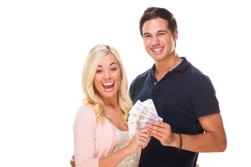 A couple stand together holding money.
