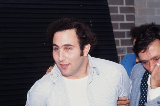 Police officers escort American accused (and ultimately convicted) serial killer David Berkowitz, known as the Son of Sam