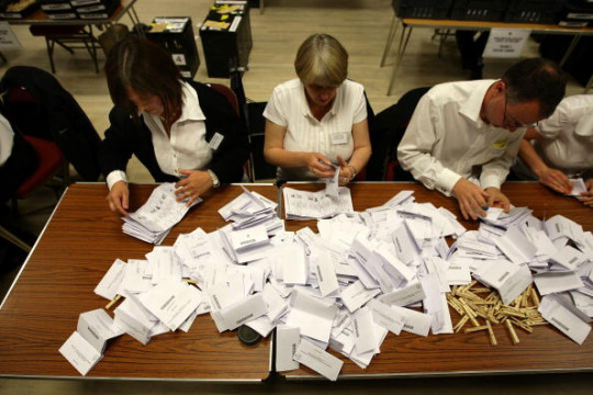 A pile of voting slips on a table, that four people are counting.