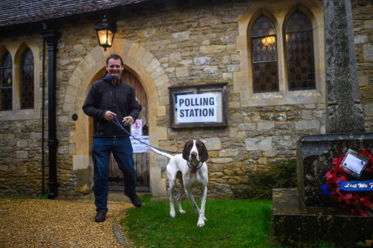 A man walking outside a church with his dog on a lead, as a sign points to a polling station.