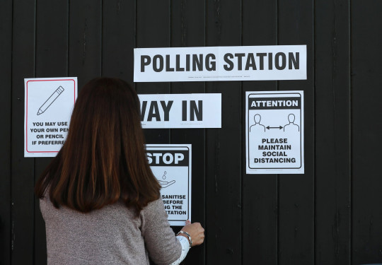A woman puts up signs advising voters to maintain social distancing at a voting station at Fulwell Mill ahead of local elections, amid the coronavirus disease (COVID-19) pandemic, in Sunderland, Britain May 6, 2021. REUTERS/Lee Smith