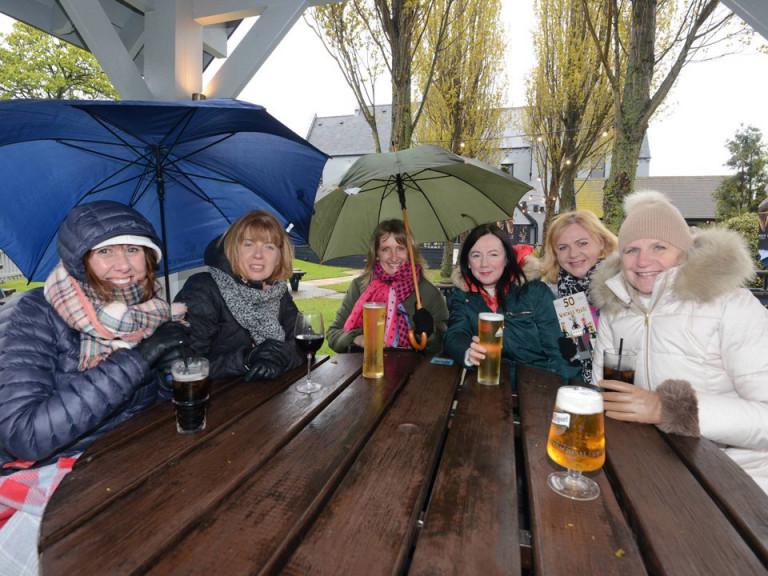 Women around a table at a beer garden with umbrellas. Brits braved the rain today and still went out and sat outside despite the weather.