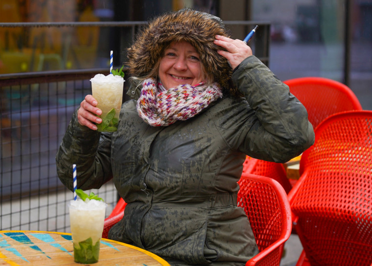 Woman having a mojito in the rain in Sheffield. Brits braved the rain today and still went out and sat outside despite the weather.