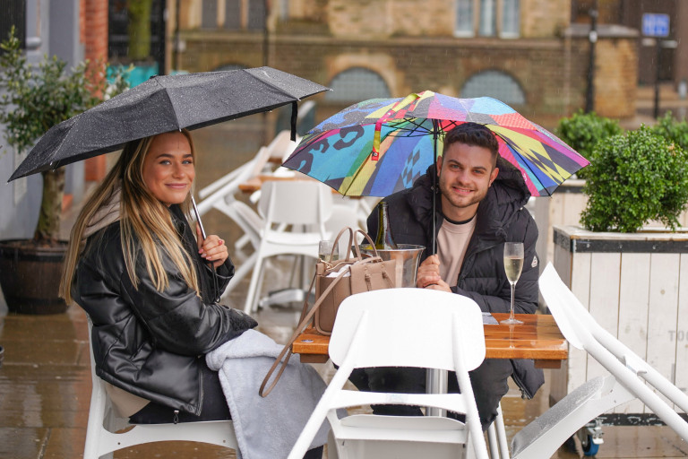A couple sitting at a table in Sheffield with umbrellas. Brits braved the rain today and still went out and sat outside despite the weather.