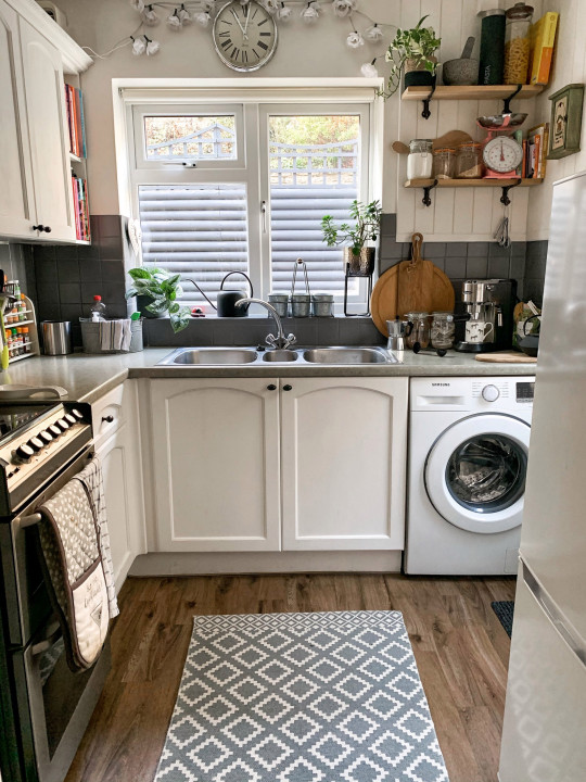 Lucy Tallyn's kitchen after she decorated it, with a greay and white colour scheme replacing multicoloured tiles
