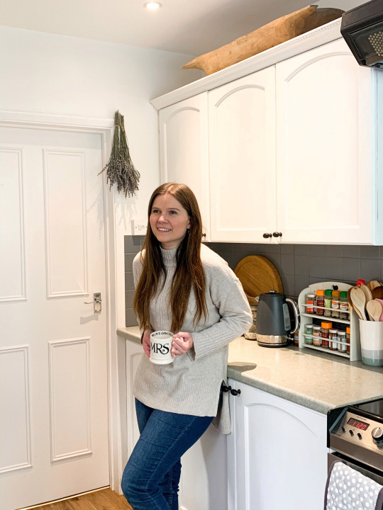 Lucy Tallyn, wearing her red hair down and a grey sweater with jeans, in her new kitchen