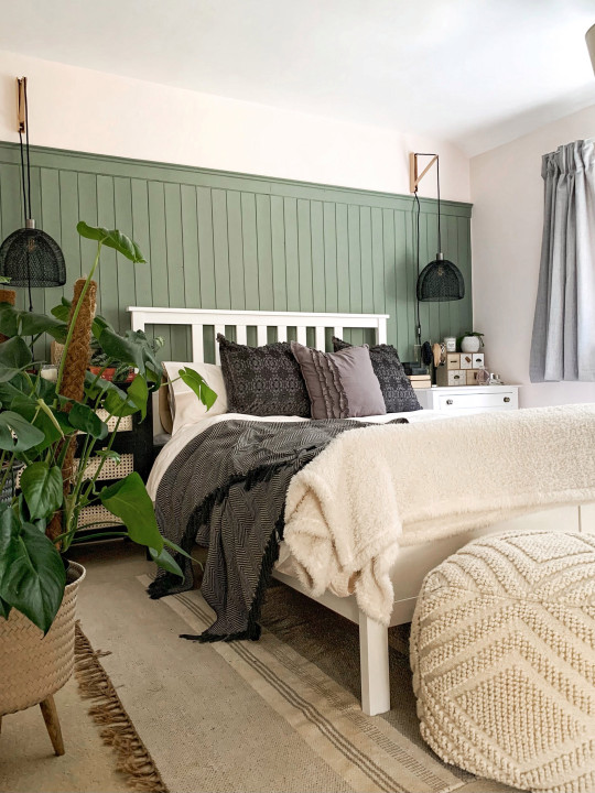 Lucy Tallyn's guest bedroom after she decorated it, with plants, green wood panels and hanging lamps