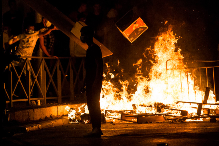 JERUSALEM, ISRAEL - MAY 08: Palestinians throw carton box to a burning barricade during clashes with Israeli police officers during the holy month of Ramadan on May 8, 2021 in Jerusalem, Israel. Tensions continue in Jerusalem's Old City after clashes in Al-Aqsa Mosque where dozens of Palestinians were seriously injured. (Photo by Amir Levy/Getty Images)