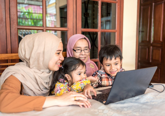 a Muslim family sitting around a laptop
