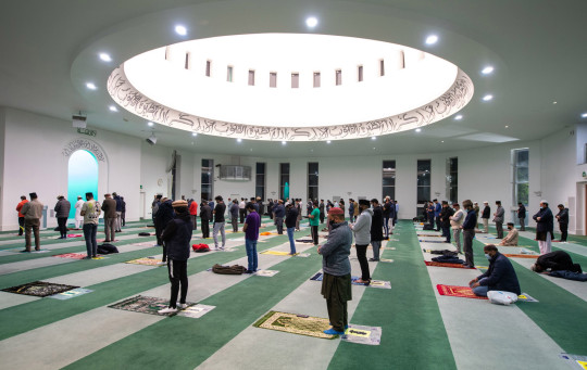 Worshippers observe social distancing during the Isha evening prayers at the Baitul Futuh Mosque, in Morden, south west London, on the final day of Ramadan, before the start of Eid al-Fitr celebrations which mark the end of the Muslim month of fasting. Picture date: Wednesday May 12, 2021. PA Photo. Muslims will celebrate Eid al-Fitr for the second year in a row under Covid-19 restrictions. See PA story RELIGION Eid. Photo credit should read: Dominic Lipinski/PA Wire