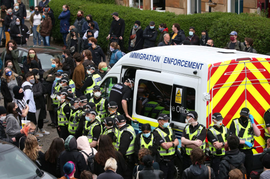 Police enter an immigration van in Kenmure Street, Glasgow which is surrounded by protesters. Picture date: Thursday May 13, 2021. PA Photo. Police were called to the Glasgow street where it is understood protesters were trying to prevent immigration officers from removing people from a property. See PA story POLICE Kenmure. Photo credit should read: Andrew Milligan/PA Wire
