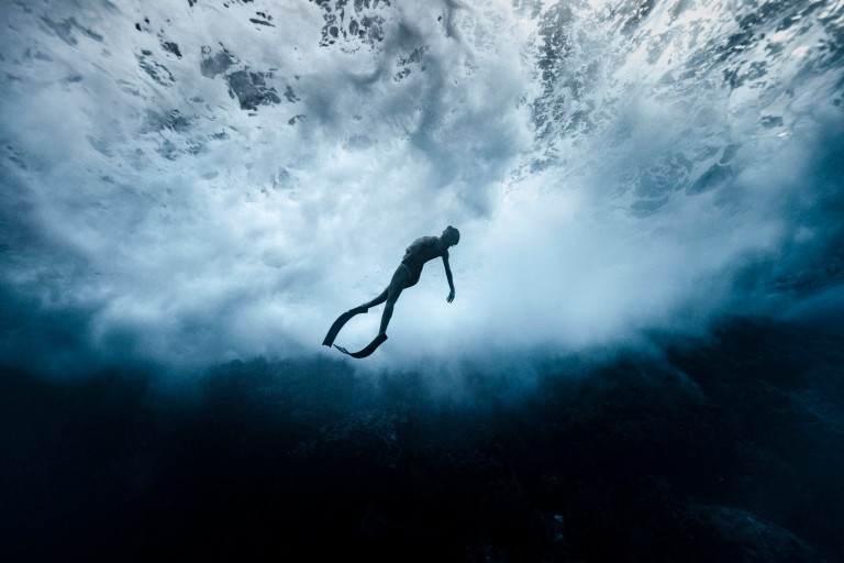 ALEX VOYER / CATERS NEWS - (PICTURED Alex Voyer photographs his wife, Marianne Aventurier, freediving underneath crashing waves off the coast of Taravao, French Polynesia. The photos give the illusion she is not swimming but flying) This woman appears to be flying without wings in the ocean. Marianne Aventurier, 42, can be seen freediving but the crashing waves in Taravao, French Polynesia, resemble the clouds. These stunning photos captured by her husband Alex Voyer, 42, create an optical illusion. It looks as though Marianne is skydiving but really she is doing pirouettes under the sea. SEE CATERS COPY