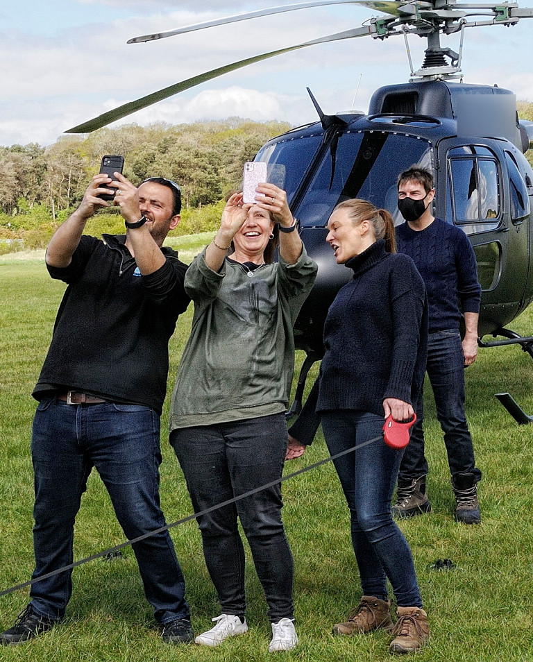 Tom Cruise seen signing autographs and taking pictures with fans as he lands in helicopter near the Mission: Impossible filmset on the outskirts of London.