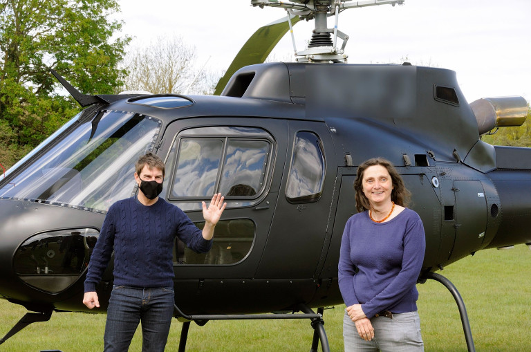 Tom Cruise with one female fan and a helicopter as he lands in helicopter near the Mission Impossible filmset on the outskirts of London.
