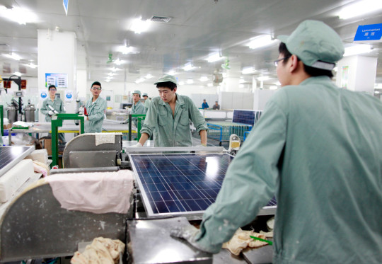 Employees assemble photovoltaic panels at Suntech Power Holdings Co.'s factory in Wuxi, Jiangsu Province, China, on Wednesday, Nov. 16, 2011. Suntech is the world's biggest maker of silicon-based solar panels while China as a whole dominates the manufacturing of solar power panels. (Photo by In Pictures Ltd./Corbis via Getty Images)
