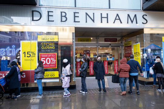 Shoppers standing outside Debenhams with closing down sale posters on its windows.  Debenhams has shut its final 28 stores as the department store closes permanently.