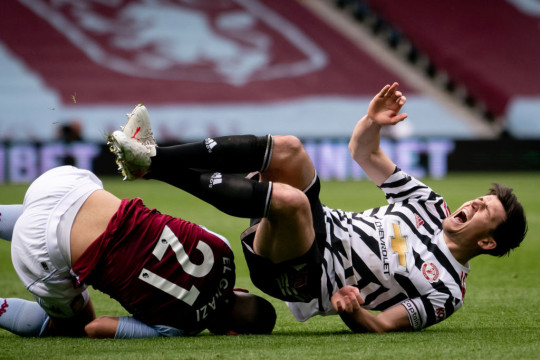 Harry Maguire is tackled during Manchester United's clash with Aston Villa