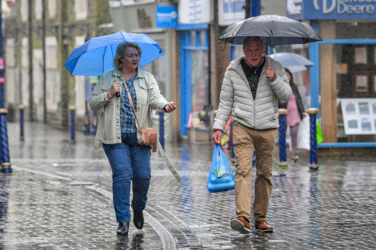 People walk past shops in Porthcawl, Wales, during a heavy downpour. Picture date: Saturday May 8, 2021. PA Photo. Photo credit should read: Ben Birchall/PA Wire