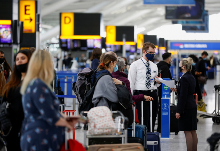 British Airways staff talk to each other as passengers stand in a queue for check-in desks in the departures area of Terminal 5