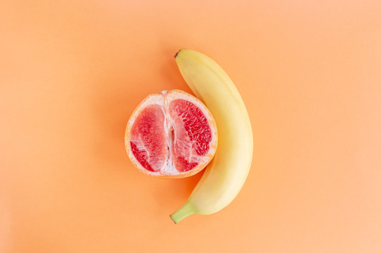 a Yellow banana and half a grapefruit on a pastel orange background