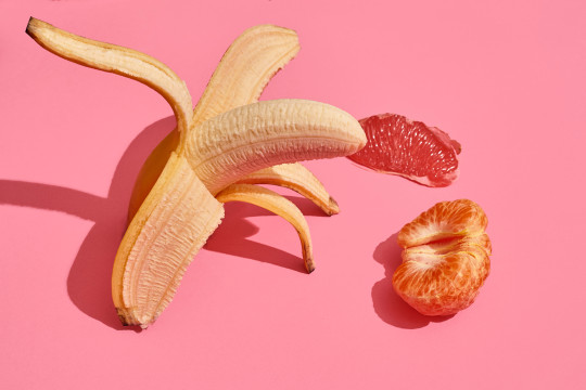 Composition of fresh fruits, whole fresh tasty banana without skin, slice of grapefruit and mandarin on pink background, top view