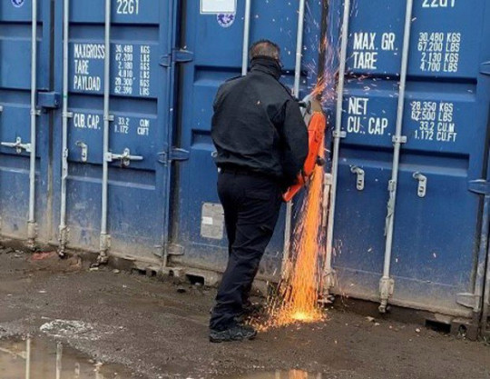 Metropolitan Police officer using a saw to break into one of the containers at the yard in Purfleet, Essex.