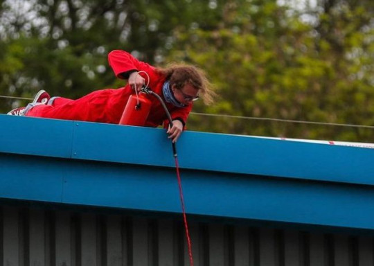 Protester pouring red paint on the factory wall. Pro-Palestine activists, who were arrested for occupying the roof of the Israeli-owned drone factory in Leicestershire, Elbit, 'have had their homes raided and their books seized by police'.