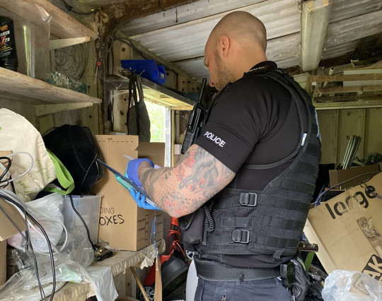 A police officer looking through boxes in a garage. Pro-Palestine activists, who were arrested for occupying the roof of the Israeli-owned drone factory in Leicestershire,Elbit, 'have had their homes raided and their books seized by police'.