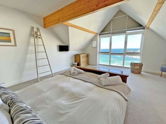 One of the four bedrooms, with views over the sea