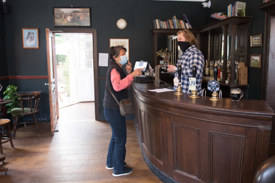 A customer at the The Carlton Tavern in Maida Vale, London places her order at the bar as indoor hospitality and entertainment venues reopen to the public following the further easing of lockdown restrictions in England. Picture date: Monday May 17, 2021. PA Photo. The pub was demolished in 2015 by a Tel Aviv based developer, who had failed to obtain the necessary planning permission, with the council subsequently ordering it to be rebuilt brick-by-brick. See PA story HEALTH Reopening Pubs. Photo credit should read: Dominic Lipinski/PA Wire