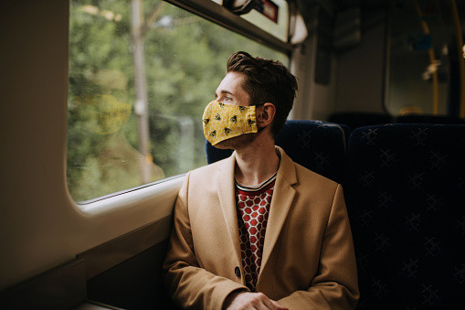Train commuter wearing PPE face mask for safety