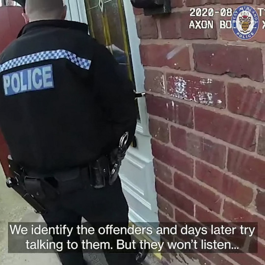 A police officer standing outside a door. Mohammed Nawaz and Raja Malik have been handed suspended jail sentences for assaulting a Dudley council worker while they were trying to issue a littering fine in Birmingham.