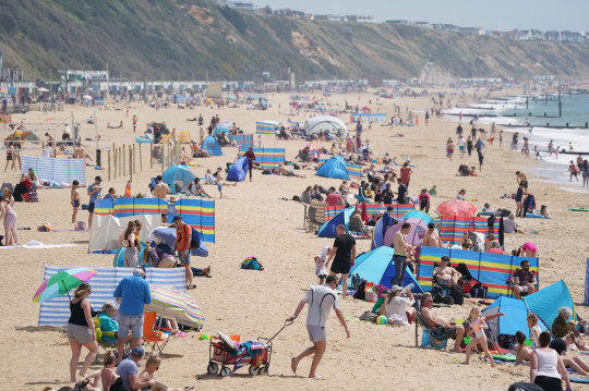 People on Boscombe beach, with the bank holiday weekend expected to bring blue skies and widespread sunshine. Picture date: Sunday May 30, 2021. PA Photo. See PA story WEATHER Spring. Photo credit should read: Andrew Matthews/PA Wire