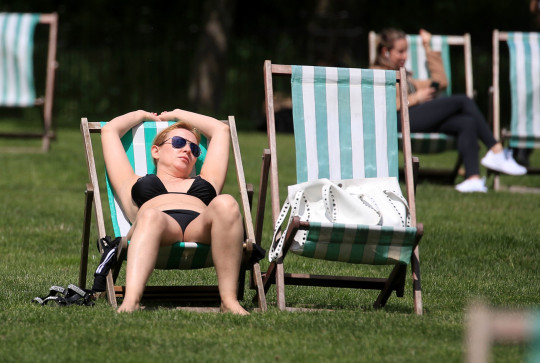 CHECK WITH PIX DESK BEFORE PUBLISHING A lady relaxes in the sunshine in Green Park, London. Picture date: Thursday May 27, 2021. PA Photo. Photo credit should read: Gareth Fuller/PA Wire