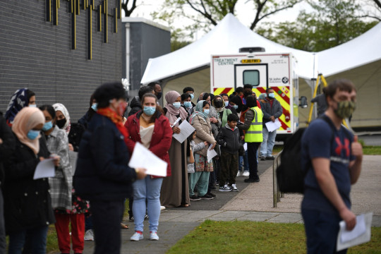 Members of the public queue at a temporary Covid-19 vaccination centre at the Essa academy in Bolton, northwest England on May 14, 2021.