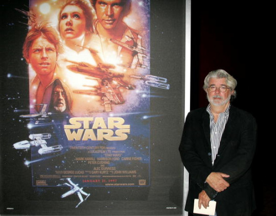 Filmmaker George Lucas wearing a white shirt and suit jacket, stood next to a poster of Star WArs.