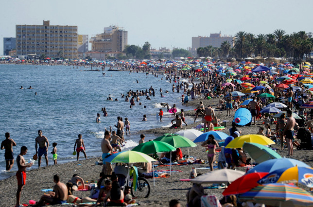 People cool off at the Mediterranean Sea on a hot spring day during the first weekend after the state of emergency decreed by the Spanish Government to prevent the spread of the coronavirus (COVID-19) was lifted, at La Misericordia beach, in Malaga, southern Spain, May 16, 2021.