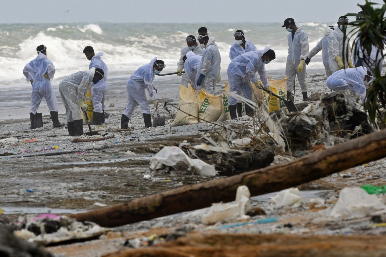 Members of Sri Lankan Navy remove debris washed ashore from the Singapore-registered container ship MV X-Press Pearl, which has been burning for the 12th consecutive day in the sea off Sri Lanka's Colombo Harbour, on a beach in Colombo on May 31, 2021. (Photo by Lakruwan WANNIARACHCHI / AFP) (Photo by LAKRUWAN WANNIARACHCHI/AFP via Getty Images)